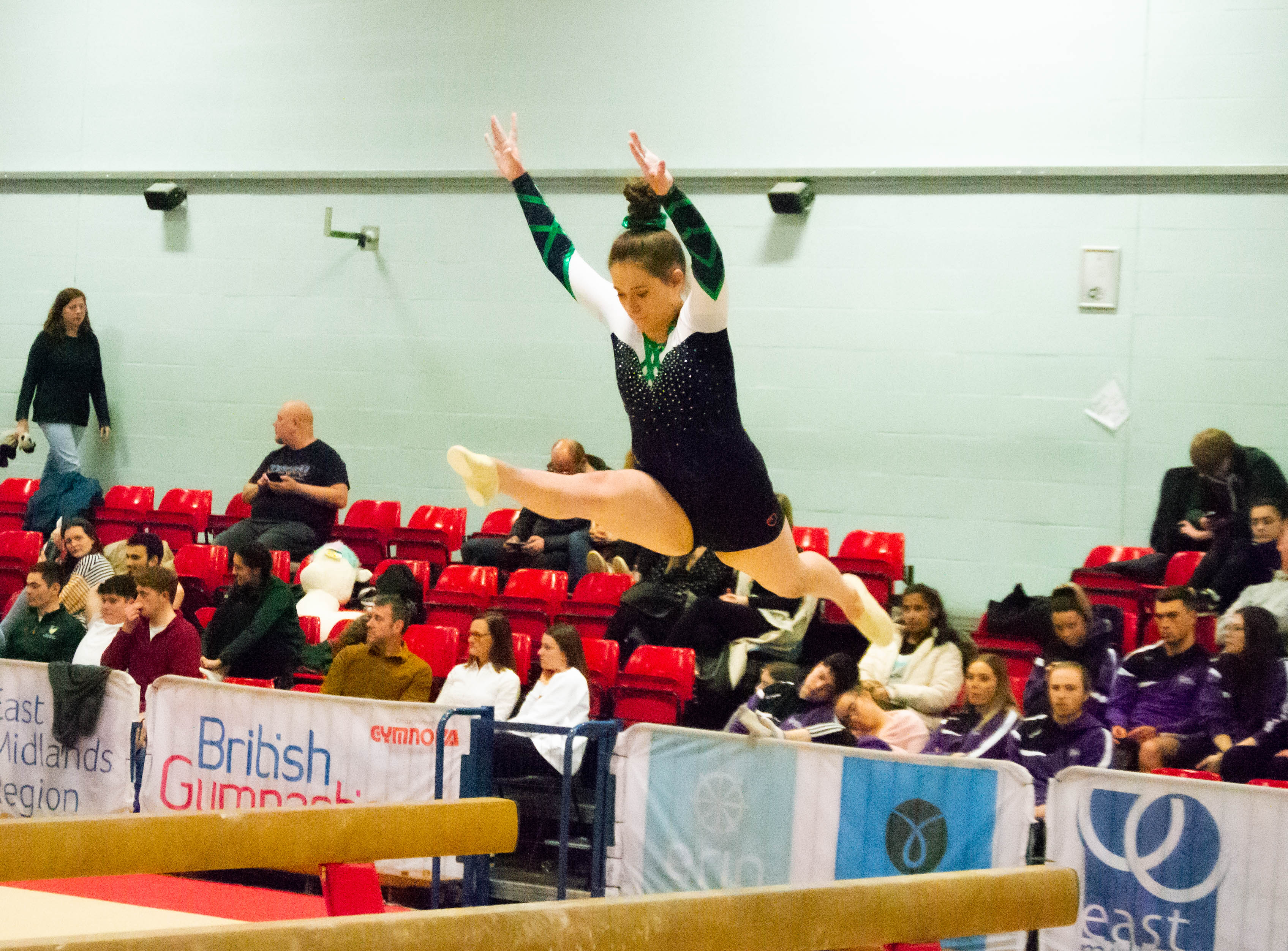 Gymnast performing a split leap on beam