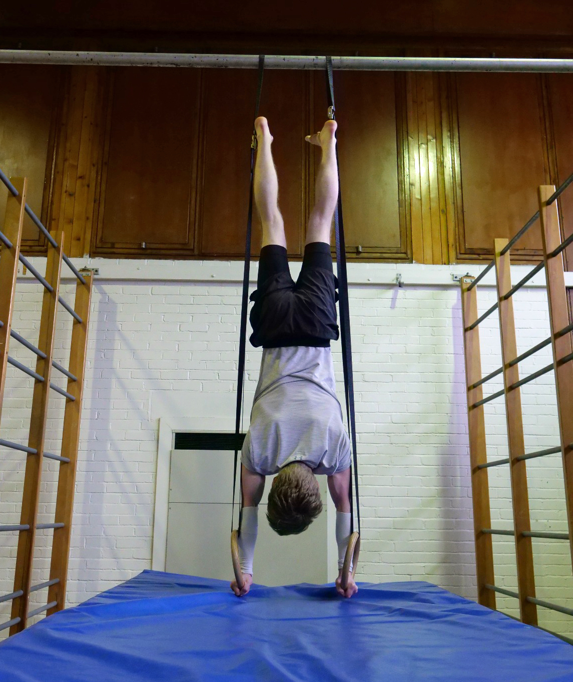 Gymnast performing a handstand on rings