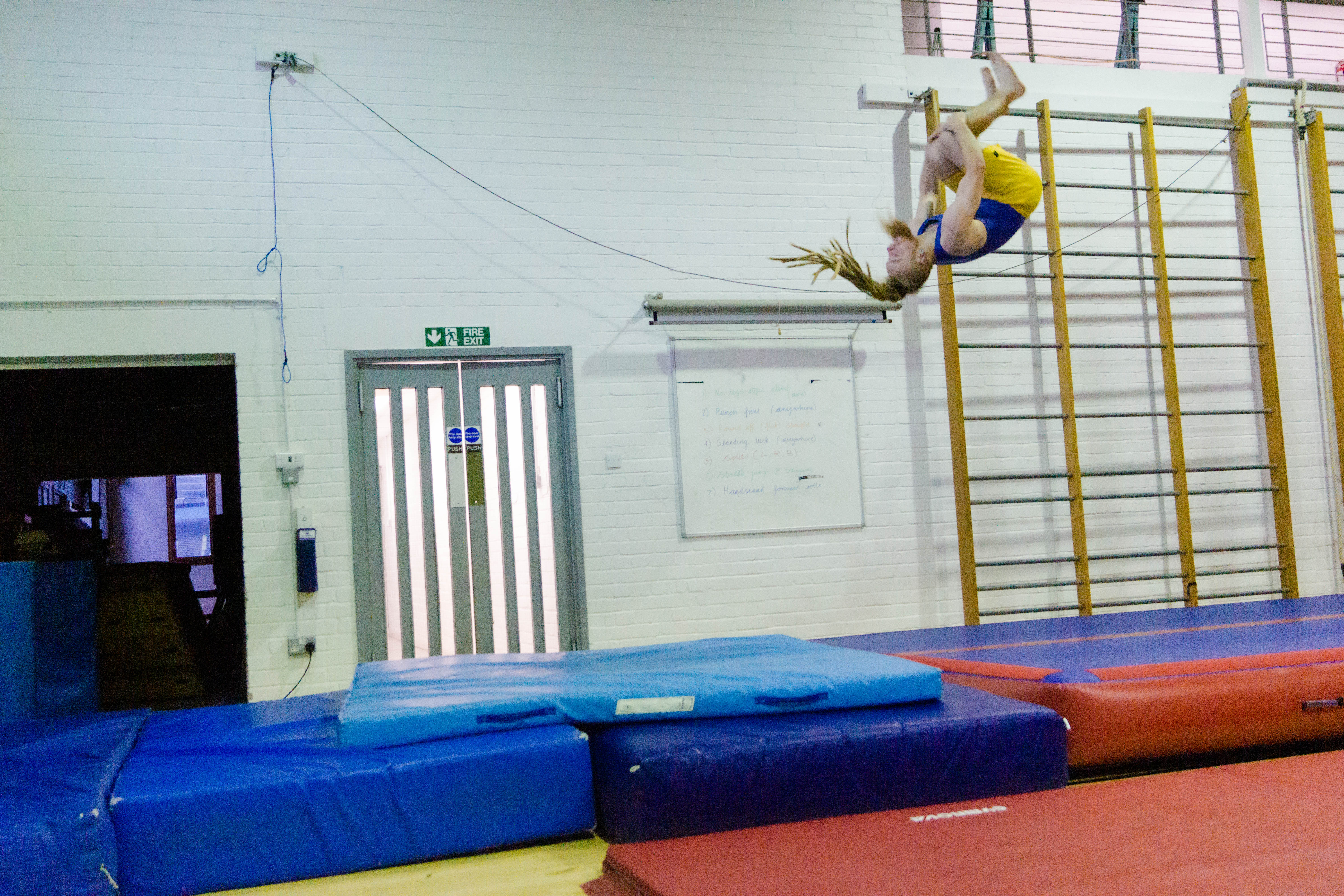 Gymnast performing a double back somersault on an air track
